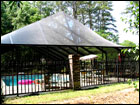 Bronze Pool Enclosure inside ornamental fencing. Steep Gable Hip Style Roof